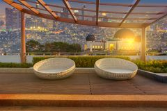 Relax corner on condominium rooftop garden with chairs on Landscape of the Griffith Observatory and Los Angeles city skyline at tw. Ilight time background royalty free stock images