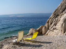 Relax on the croatian beach. Deckchairs on the rocky and pebbles beach in Croatia Stock Photos