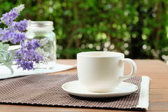 Relax with a cup of coffee in the garden. Coffee on wood table in the green garden Stock Image