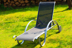 Relax. Empty deck chair on grass in garden. Stock Image