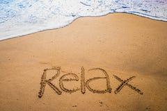 Relax escrito na areia em uma praia Fotos de Stock Royalty Free