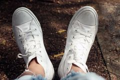A relax feet of young woman in white sneakers background. Inspirations concept with copy space. Human body part in casual style royalty free stock photography