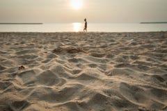 Relax gehend auf den nassen sandigen Strand während des Sonnenuntergangs Stockfotografie
