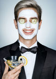 Relax. Gentleman with glass of martini and cosmetic mask on the face. Stock Photo