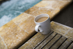 A cup of coffee with Creamer next to a spa. A good cup of coffee in the morning next to the pool Royalty Free Stock Photos