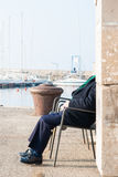 Relax at the harbor. An old man relaxing on a chair at the harbor of Trieste Stock Images