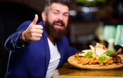 Relax after hard day. Delicious food. Businessman formal suit sit at restaurant. Man received meal with fried potato. Fish sticks meat. He deserve delicious stock photography