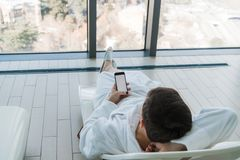 Relax in the hotel with a phone in hand. A man lying on a lounger by the pool and enjoying smartphone and great city royalty free stock image