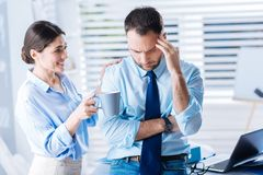 Optimistic woman helping her upset colleague to cheer up and relax. Relax. Kind emotional positive women smiling and offering her irritated upset colleague a cup Stock Photo