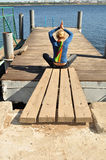 Relax, leisure, meditation. Coast, the girl spends his free time, she sits on the pier overlooking the water, the photograph is a place for advertising slogan Royalty Free Stock Image