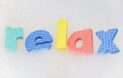 Relax letters in bubble bath foam. Abstract stock photo