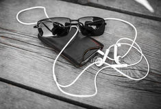 Relax and Listen to Music. A pair of sun glasses and a mobile music player with white headphones on wooden surface Stock Images