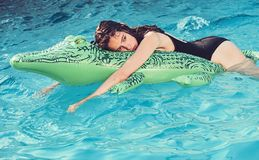 Relax in luxury swimming pool. Fashion crocodile leather and girl in water. Summer vacation and travel to ocean stock photo