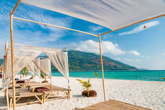 Relax on a luxury VIP beach with nice pavilions in a sunshine bl Royalty Free Stock Photos
