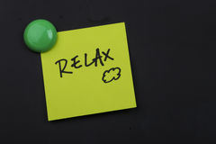 Relax note on blackboard. Close up of a post-it note saying relax on blackboard background Stock Photography