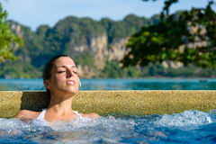 Relax in outdoor spa pool. Beautiful relaxed woman enjoying spa pool at resort in Thailand. Relaxing outdoor jacuzzi stock photography