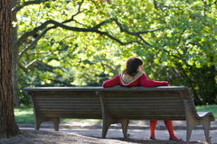 Relax in the park. Girl is sitting on the bench in the park Royalty Free Stock Photos