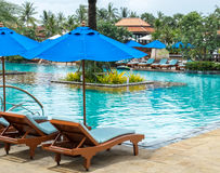 Relax by The Pool in Luxury Hotel on The Island of Thailand. Couple of Wooden Chair under The Umbrella Royalty Free Stock Image