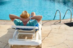 Relax in the pool summer. Young and successful man lying on a sun lounger at the hotel on the background of sunset stock photography