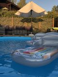 Relax by the poolside on a floating mattress in the sunset stock photo