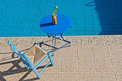 Relax at poolside. Table and chair beside waterpool Royalty Free Stock Photography