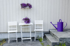 Relax on the porch. Arrangement of chairs, table and flowers - White and purple Royalty Free Stock Images