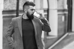 Relax and recharge. Man bearded hipster drinking coffee paper cup. One more sip of coffee. Drinking coffee on the go royalty free stock images