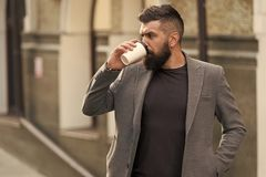 Relax and recharge. Man bearded hipster drinking coffee paper cup. One more sip of coffee. Drinking coffee on the go stock image