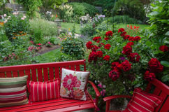 Relax in Red. Overlooking a colorful backyard garden with casual red furniture and geraniums.in the foreground Royalty Free Stock Images