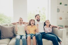Relax, rest, carefree, careless concept. Photo of single father. With adopted kids pre-teen preteen with raised hands up sit on soft cozy, comfort couch in stock images