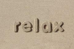 Relax scritto nelle lettere della sabbia Fotografia Stock