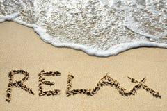 Relax scritto sulla spiaggia sabbiosa vicino al concetto marino di festa Immagine Stock Libera da Diritti