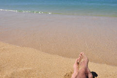 Relax by the Sea. Closeup of man s feet in sea shore Royalty Free Stock Photo