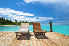 Relax by the sea. Two wooden deck chairs at a tropical resort, Maldives Stock Image