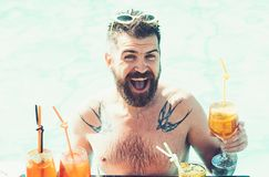 Relax at sea and spa resort. Cocktail party with bearded man in pool. Pool party with hipster in blue water. Man stock photography