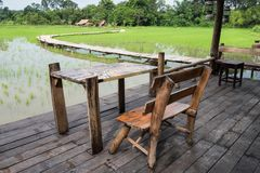 Wooden terrace near paddy rice field. Relax seats at wooden terrace near paddy rice field in rainy season, Nakhon Nayok, Thailand Stock Photo