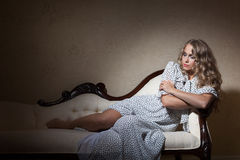 Relax. Sensual blonde woman in retro polka dot dress laying on the coach Royalty Free Stock Photo