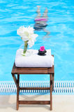 Relax in Spa. Spa in summer with woman relaxing in swimming pool, towel and flowers Royalty Free Stock Photography