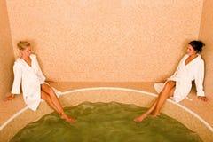 Relax spa pool two women sitting bathrobe Stock Photography