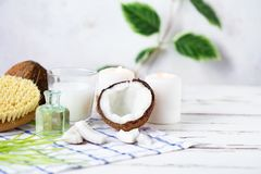 Relax and spa theme. Coconut, coconut oil, milk, candles, massage brush. On a bright, summer background royalty free stock photo