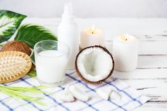 Relax and spa theme. Coconut, coconut oil, milk, candles, massage brush. On a bright, summer background royalty free stock photos