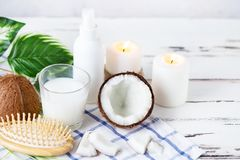 Relax and spa theme. Coconut, coconut oil, milk, candles, massage brush. On a bright, summer background stock photos