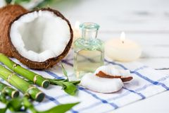 Relax and spa theme. Coconut, coconut oil, bamboo, candles, massage brush. On a bright, summer background royalty free stock image