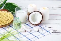 Relax and spa theme. Coconut, coconut oil, milk, candles, massage brush. On a bright, summer background royalty free stock image