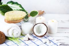Relax and spa theme. Coconut, coconut oil, milk, candles, towel ,massage brush. On a bright, summer background royalty free stock photos