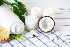 Relax and spa theme. Coconut, coconut oil, milk, candles, towel ,massage brush. On summer background stock images