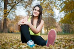 Relax - sportswoman sitting in grass Royalty Free Stock Photos