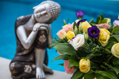 Relax statuette Buddha with flower on pool background. Relax statuette Buddha with flower on blue pool background Stock Image