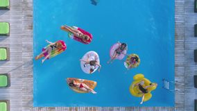 Relax in summer pool, cheerful company of woman friends swim on Inflatable rings and mattress at poolside in expensive