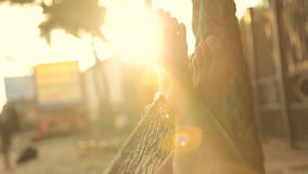 Relax at sunset. Men`s feet swinging in a hammock under palms on the beach. POV stock video